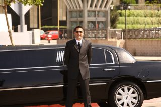 Professional chauffeur standing next to his stretch limousine.